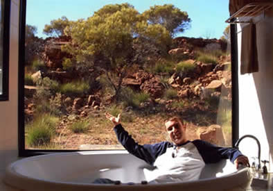 Craig sitting fully clothed in a luxury bathtub, opening his arms in a magnanimous gesture