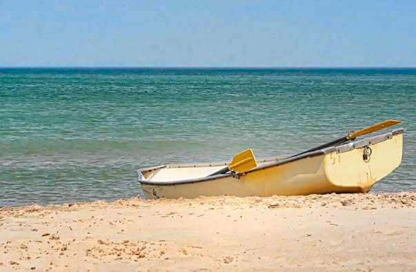 A photograph of a yellow boat on a beach in front of a blue-green ocean. Link to the Fiction section.